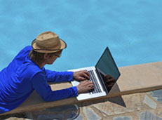 Man relaxing on his laptop by a pool